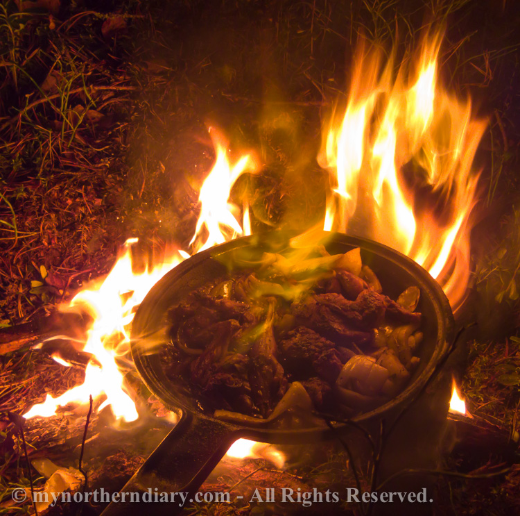 Frying the hazel grouse in sweet whiskey on a camp fire with casted iron pan