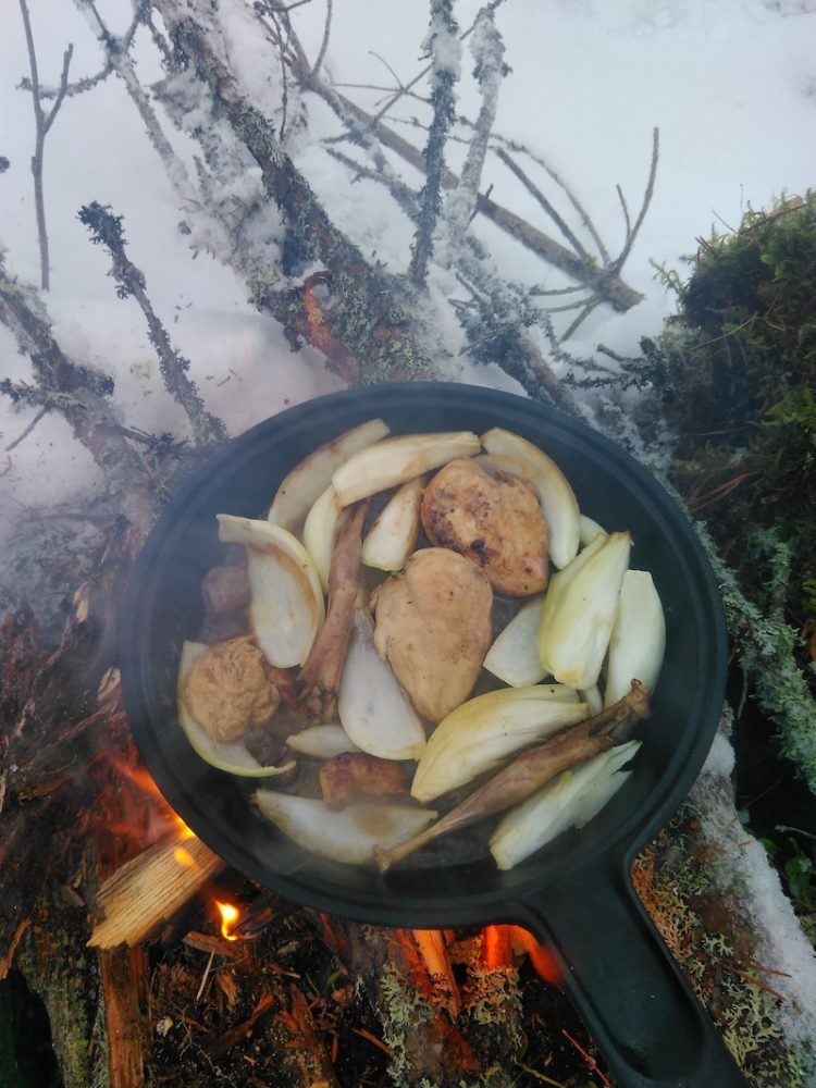 Cooking game birds at campfire in winter