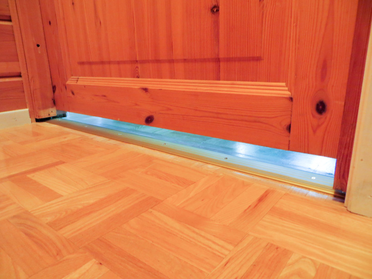 Lower door frame golden aluminum moulding harmonious with warm wood panels